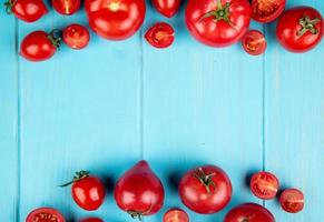 Top view of whole and cut tomatoes on blue background with copy space photo