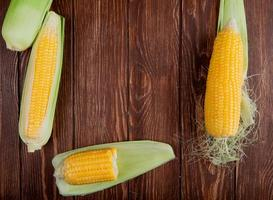 top view of cut and whole corns with shell on wooden background with copy space photo