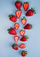 Top view of whole and cut strawberries on blue background