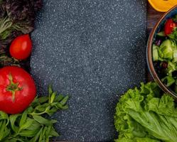 Vista superior del corte y verduras enteras como tomate albahaca menta pepino lechuga con tabla de cortar como fondo foto