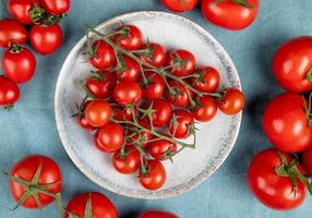 top view of little tomatoes in plate with other ones on blue background photo