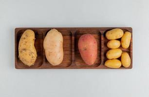 top view of different types of potato on white background