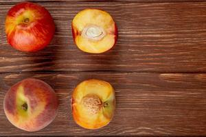 Top view of pattern of whole and half cut peaches on wooden background with copy space