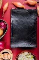 Vista superior de diferentes cebollas enteras y en rodajas y pimienta negra en trituradora de ajo alrededor de la placa sobre fondo rojo.