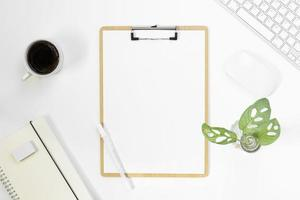 Minimal Office desk table top view with office supply and coffee cup on a white table with copy space, White color workplace composition, flat lay photo