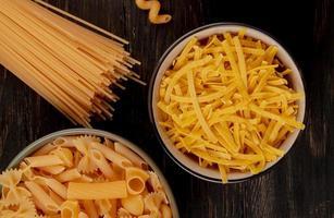 Vista superior de diferentes tipos de macarrones como tallarines y otros en tazones con tipo espagueti sobre fondo de madera foto
