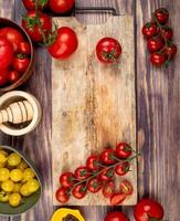 top view of cut and whole tomatoes on cutting board with other ones black pepper garlic crusher on wooden background photo