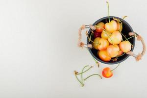 Top view of pot full of cherries and stems on right side and white background with copy space