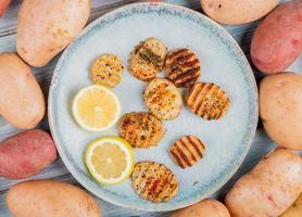 Vista superior de rodajas de patata frita y rodajas de limón en un plato con patatas blancas y rojas alrededor sobre fondo de madera