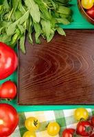Vista superior de verduras como hojas de menta verde tomates alrededor de la bandeja vacía sobre fondo verde foto