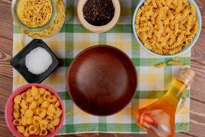 top view of different macaronis in bowls and jar salt black pepper butter around bowl on plaid cloth and wooden background