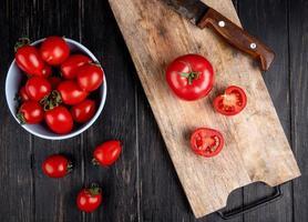 Vista superior del corte y los tomates enteros y un cuchillo sobre la tabla de cortar con otros en un tazón sobre fondo de madera
