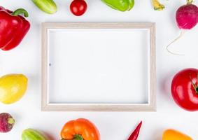 top view of vegetables as pepper cucumber radish tomato with frame on white background with copy space photo