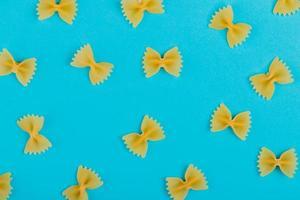 Vista superior del patrón de pasta farfalle sobre fondo azul. foto