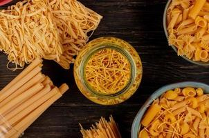 top view of different types of macaroni as bucatini spaghetti vermicelli tagliatelle and others on wooden background