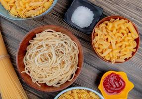 Different macaronis as spaghetti rotini vermicelli and others with salt and ketchup on wooden background