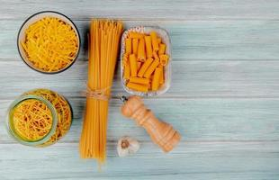 top view of different types of macaroni as tagliatelle spaghetti vermicelli ziti and others with garlic salt on wooden background with copy space