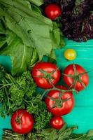Verduras como hojas de menta verde tomate albahaca sobre fondo verde foto
