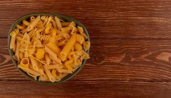 Macaroni in bowl on wooden background with copy space