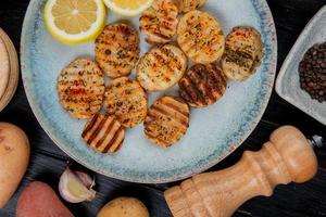 top view of fried ruffled potato slices and lemon slices in plate with whole ones garlic black pepper seeds and salt on wooden background photo