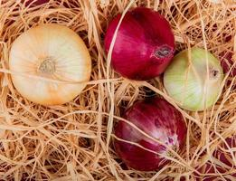 Top view of sweet, red and white onions on straw background
