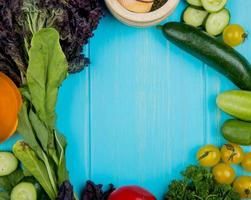 top view of vegetables as spinach basil cucumber tomato coriander with garlic crusher on blue background with copy space