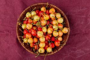 top view of basket full of yellow and red cherries on bordo cloth background