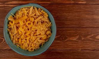 top view of different types of macaroni in bowl on wooden background with copy space