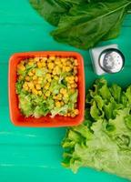 top view of bowl of yellow pea with sliced lettuce and spinach salt whole lettuce on green background