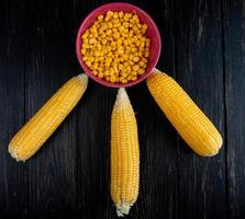 top view of cooked corns with bowl of cooked corn seeds on black background