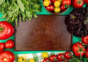 Vista superior de verduras como hojas de menta verde tomate albahaca alrededor de la bandeja vacía sobre fondo verde foto