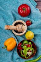 Vista superior de las verduras como pimientos y tomates enteros y en rodajas con limón y pimienta negra en trituradora de ajo sobre fondo de tela azul foto