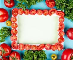 Vista superior de tomates cortados a bordo con otros y cilantro sobre fondo azul con espacio de copia