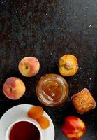 top view of glass jar of peach jam with peaches cupcakes and cup of tea on black and brown background with copy space