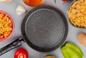 Vista superior de diferentes tipos de macarrones como cavatappi y otros con ajo, tomate, mantequilla, pimienta alrededor de la sartén sobre fondo púrpura foto
