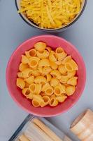 top view of different types of macaroni in bowls as pipe-rigate tagliatelle bucatini on blue background