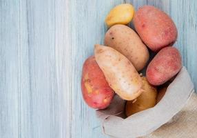Top view of russet red and new potatoes spilling out of sack on wooden background with copy space photo
