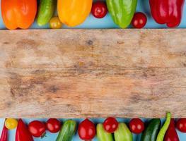 pimientos, tomates y pepinos con una tabla de cortar sobre un fondo azul. foto