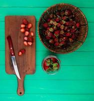 top view of cut strawberries with knife on cutting board and whole strawberries in basket and bowl on green background