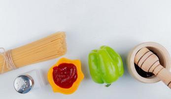 Vista superior de fideos macarrones con pimienta negra ketchup pimienta sobre fondo blanco.