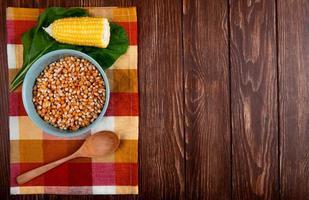 Vista superior del tazón de grano de maíz seco con cuchara de madera de maíz cocido y espinacas sobre tela y fondo de madera con espacio de copia