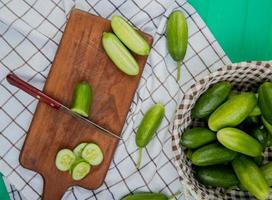 top view of cut and sliced cucumber with knife on cutting board with whole ones in basket on plaid cloth and green background