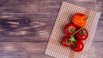 Vista superior de verduras como pimiento y tomates en tela escocesa en el lado derecho y fondo de madera con espacio de copia