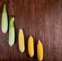 Cooked and uncooked corn cobs on left side and wooden background with copy space photo