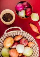 Vista superior de diferentes cebollas en la canasta con otras en un tazón y semillas de pimienta negra sobre fondo rojo. foto