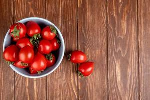 Top view of tomatoes in bowl with other ones on left side and wooden background with copy space
