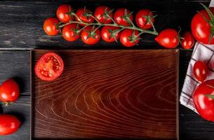 top view of half cut tomato in tray and whole ones on wooden background