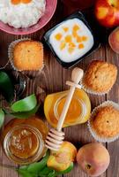 top view of jars of jams as peach and plum with cupcakes peaches cottage cheese on wooden background