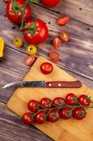 Cut and whole tomatoes with knife on cutting board on wooden background