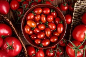 Top view of tomatoes in bowl basket and plate on wooden background